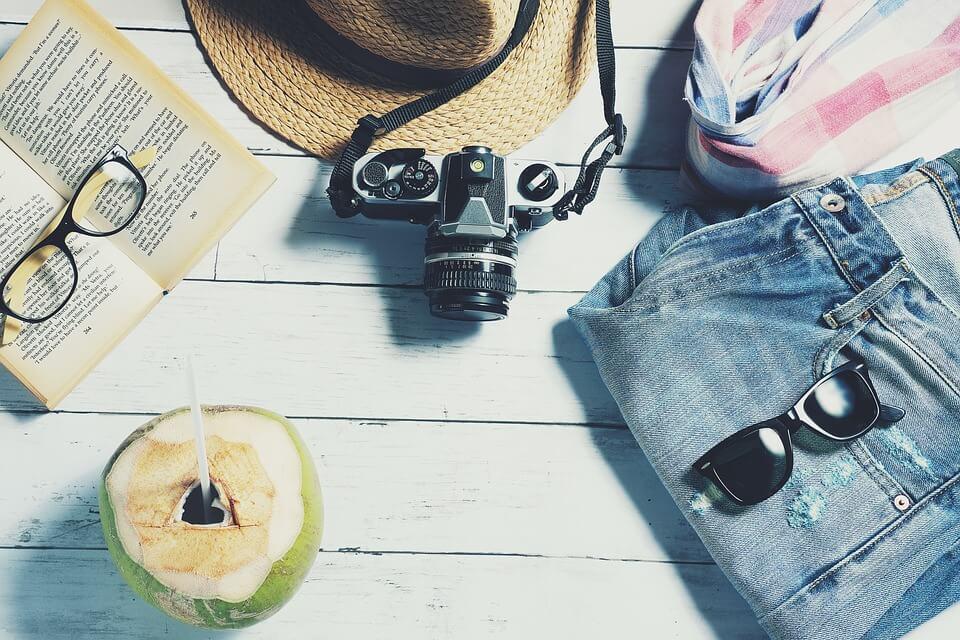 Gepäck für Reisen: Kamera, Sonnenhut, Buch, Sonnenbrille und Shorts