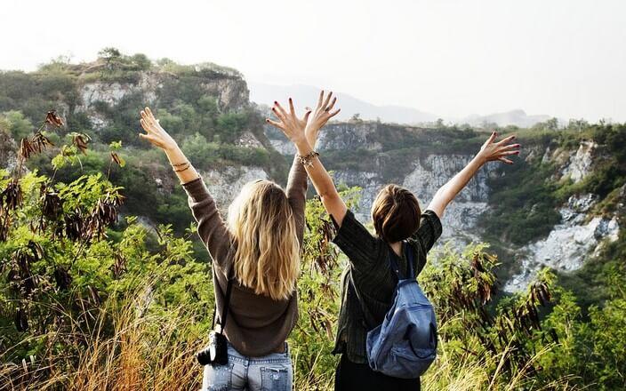 Zwei Mädchen auf Reisen mit Rucksack und Kamera