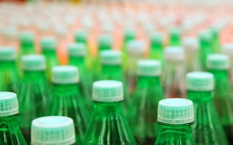 grüne Mehrweg Plastikflaschen im Vordergrund, orange Flaschen dahinter