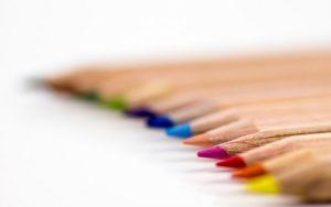 Buntstifte aus unlackiertem Holz in Reihe hintereinander gelegt
