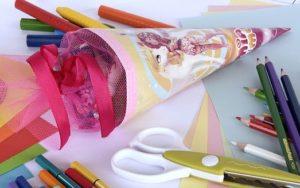 Schulanfang mit Schultüte und Schreibwaren wie Buntstifte, Filzstifte und Bastelschere