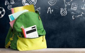 Schulanfang mit Schulranzen gefüllt mit Schulsachen vor Kreidetafel
