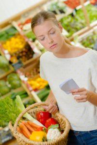 Junge Frau überprüft mit einem Blick auf ihre Einkaufsliste, ob sie alle Einkäufe beisammen hat. In ihrem mitgebrachten Korbst befindet sich frisches Gemüse unverpackt.