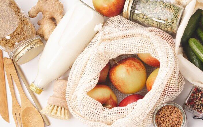 Zero Waste Konzept mit wiederverwendbaren Gemüsenetzen, Einmachgläsern, Holzprodukten