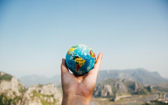 Hand hält kleine Weltkugel vor Panorama in der Hand