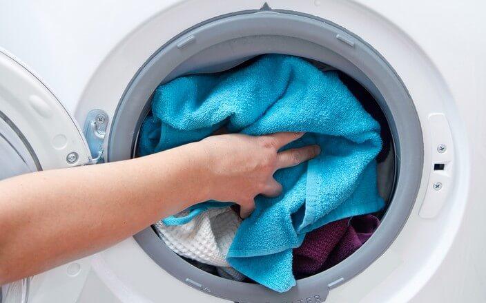 Waschmaschine wird mit Textilien aus Kunststofffasern befüllt