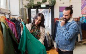 Mann und Frau schauen sich beim Shoppen in Second-Hand Laden einen grünen Mantel an