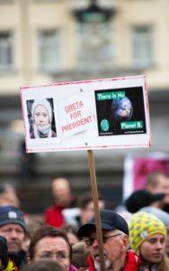 """Klimaaktivist hält Schild mit Aufschrift """"Greta for president"""" und """"There is no Planet B"""" in einem Klimastreik in die Höhe"""
