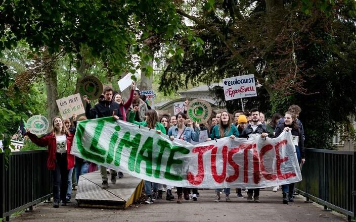 """Gruppe von Kindern und Jugendlichen zieht mit Banner mit der Aufschrift """"Climate Justice"""" und vielen Schildern durch die Straßen"""