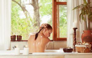 Frau von hinten in Badewanne seift sich die Haare mit plastikfreier Haarseife ein