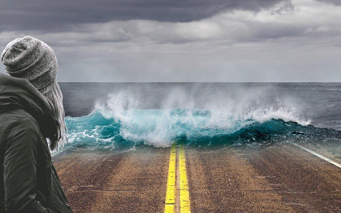 Überschwemmungswelle als Auswirkung vom Klimawandel rollt über Straße auf Person zu
